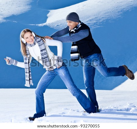 Happy couple having fun, running jumping catching fight game, playing outdoors at winter snowy mountains, people at nature, Christmas vacation holidays, love concept