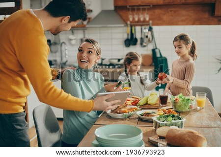 Happy couple having fun while using touchpad at dining table while their daughters are in the background. Focus s on woman.  Stock fotó ©