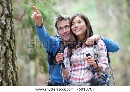 Happy couple hiking outdoors in forest. Active young asian woman hiker and caucasian man.