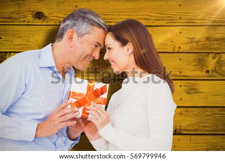 Happy couple holding gift against green paint splashed surface #569799946