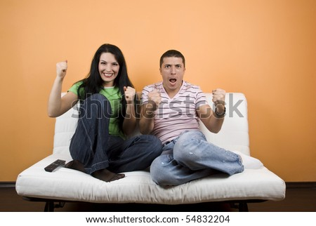 Happy couple home  watching TV their favorite sport team  or favorite match over television and they exclaim  gladly  :GOAL