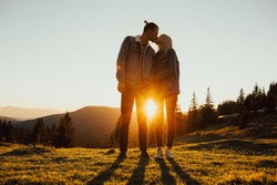 Happy couple hugging and kissing at sunset with amazing mountain view. Warm evening, sun light, couple hug together and close to a pine forest.  Sun between the legs of a couple. Copy space.