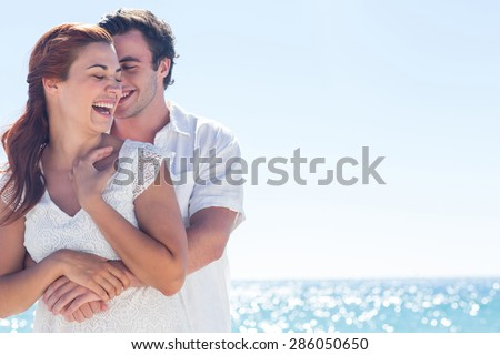 Happy couple hugging and laughing together at the beach #286050650