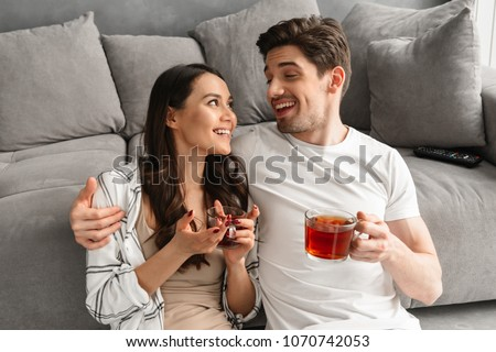 Happy couple hugging and looking at each other while sitting on floor in living room and drinking tea from glasses