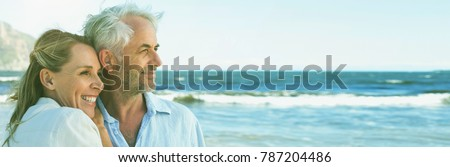 Photo of Happy couple hugging on the beach looking out to sea on a sunny day