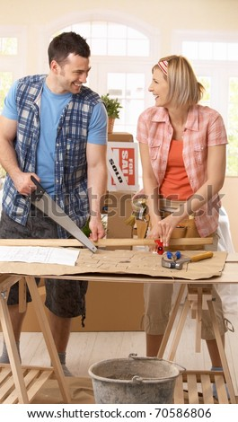Happy couple improving new house, working together at table.?