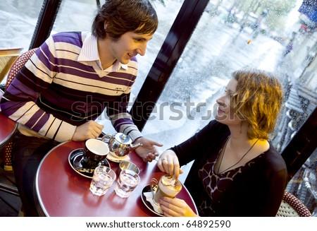 Happy couple in a Parisian cafe at rain