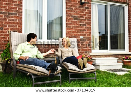 Happy couple in backyard of new home sitting on lounge chairs