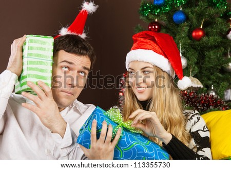 Happy couple in Christmas hats near the Christmas tree