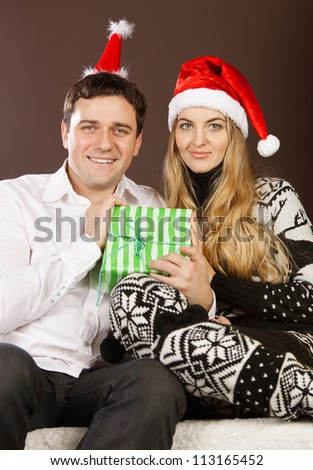 Happy couple in Christmas hats with presents