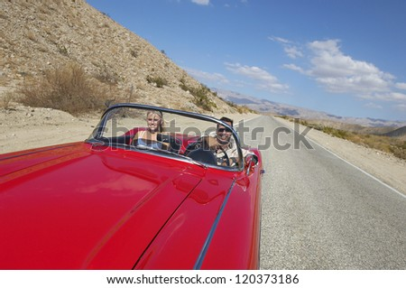 Happy couple in classic car on road