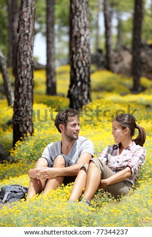 Happy couple in forest sitting smiling around flowers. Beautiful young couple: Asian woman, Caucasian man. Photo from Tenerife, Spain.