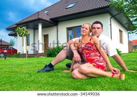 Happy couple in front of their ideal house