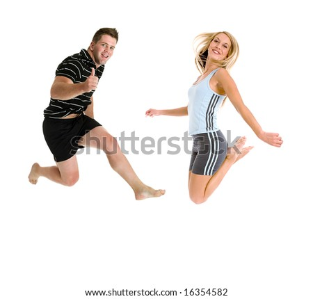 Happy couple in gym clothes jumping with joy over a white backdrop
