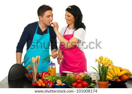 Happy couple in kitchen,woman giv ing man to eat vegetables