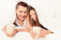 Happy couple in love basking with blanket and hot tea