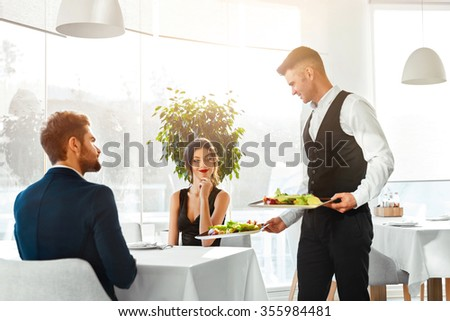 Happy Couple In Love Having Romantic Dinner In Luxury Gourmet Restaurant. Waiter Serving Meal. People Celebrating Anniversary Or Valentine\'s Day. Romance, Relationship Concept. Healthy Food Eating.
