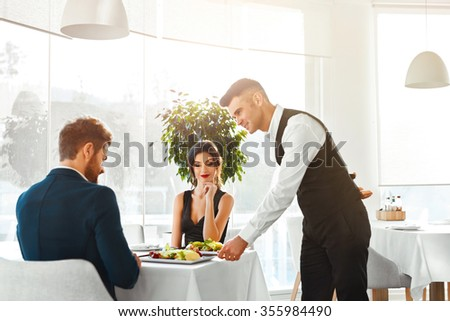 Happy Couple In Love Having Romantic Dinner In Luxury Gourmet Restaurant. Waiter Serving Meal. People Celebrating Anniversary Or Valentine's Day. Romance, Relationship Concept. Healthy Food Eating.