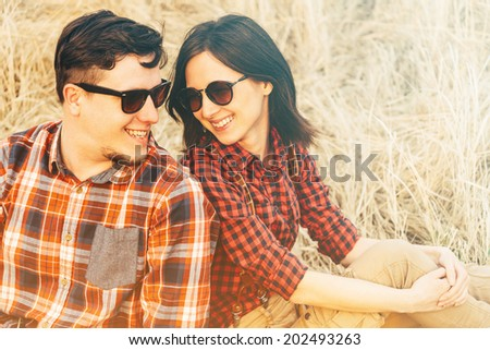 Happy couple in love is sitting on hay, hipster style