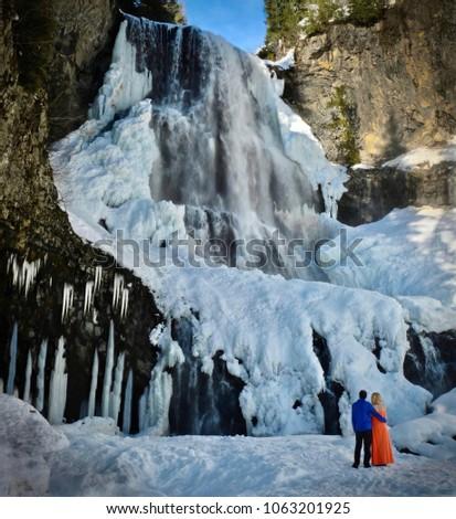 Happy couple in love near waterfall. Frozen waterfall near Callahan Olympic Park.  Alexander Falls. Whistler. British Columbia. Canada.