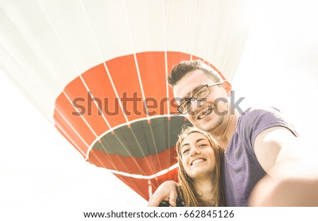 Happy couple in love on honeymoon vacation taking selfie at hot air balloon - Summer travel concept with young people travelers having fun at excursion - Vintage contrast retro filter with backlight