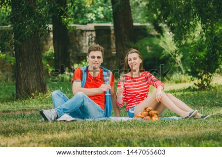 Happy couple in love resting in the park on the meadow. couple of young people are sitting on a bed in a park in the summer and drinking champagne from glasses. Outdoor activities, outdoor activities