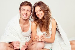 Happy couple in love sitting in bed with blanket and coffee