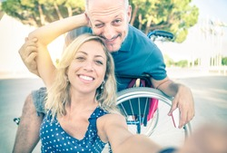Happy couple in love taking selfie in urban city background - Disability positive concept with man on wheelchair - Vintage filtered look with soft focus on smiling woman due to sun flare halo