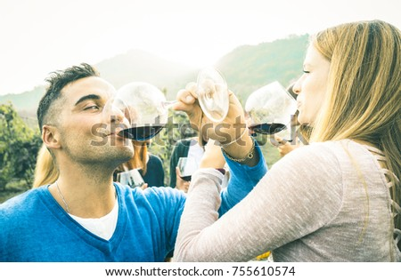 Happy couple in love toasting red wine at vineyard farmhouse - Young man drinking and looking at beautiful woman eyes - Unplugged relationship concept with boyfriend and girlfriend having fun together