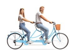 Happy couple in matching outfits riding a tandem bicycle isolated on white background