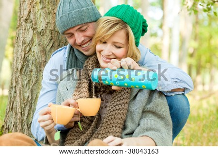 Happy couple in nature drinking tea outdoors having picnic in fall season smiling laughing