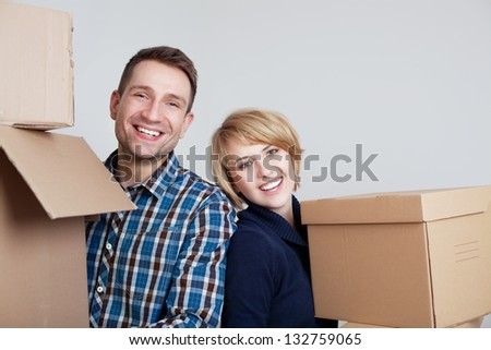 Happy couple in new home holding boxes