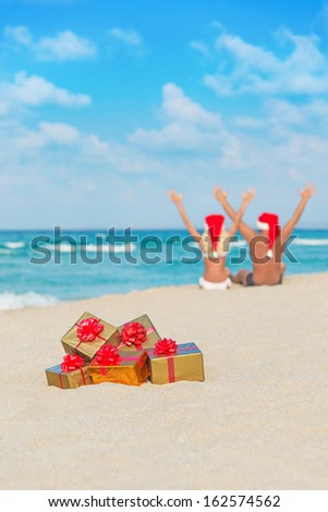 happy couple in santa hats hands up at sea beach with christmas packed  golden gifts