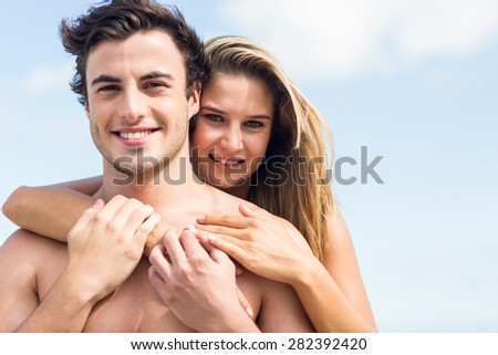 Happy couple in swimsuit embracing at the beach