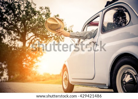 Happy couple in the car driving for a journey in the countryside