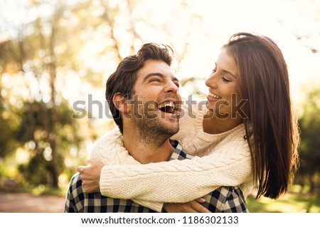 Happy couple in the park looking at each other and laughing