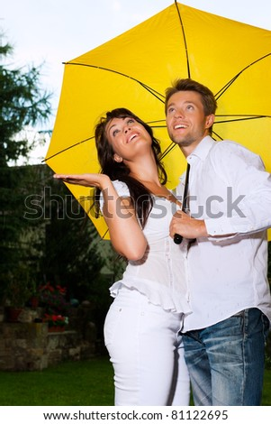 Happy couple in the summer rain with a yellow umbrella