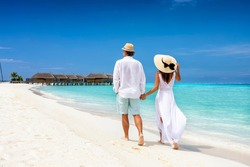 Happy couple in white clothing and with hats walks down a tropical beach with turquoise sea in the Maldives islands