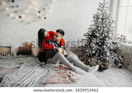 Photo of  Happy couple in winter sweaters having fun lying on cozy bed and laughing, woman hugging her boyfriend spending winter holidays at home in warm christmas atmosphere