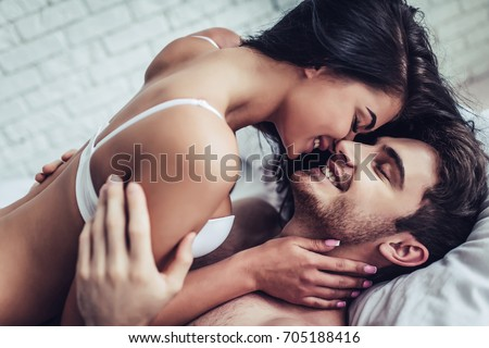 Happy couple is lying in bed together. Enjoying the company of each other.