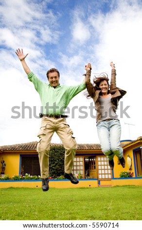 happy couple jumping of joy outside their home