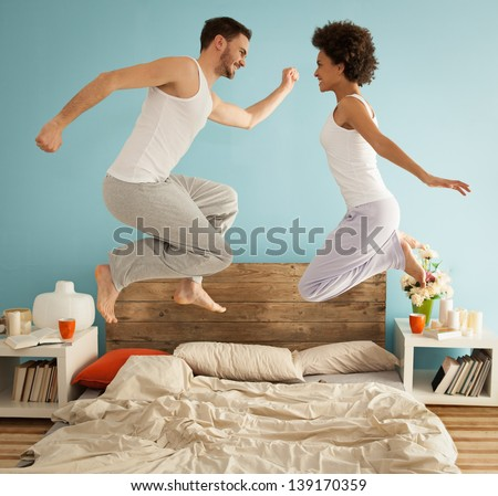 Happy couple jumping together on their bed.