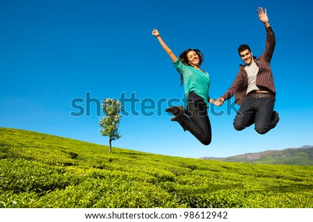 Happy couple jumping with hands raised in green field.