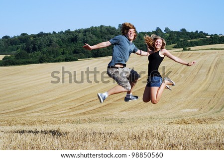 happy couple jumps outdoors in summer