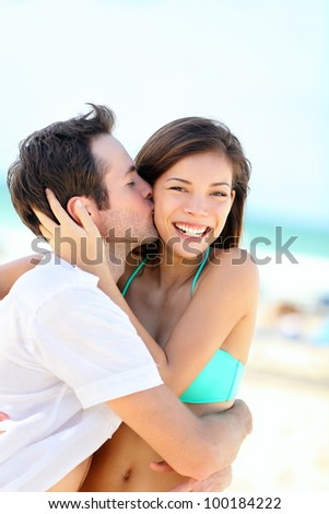 Happy couple kissing and embracing in joyful happiness showing love during summer beach vacation. Beautiful young interracial couple, Asian woman, Caucasian man outdoors.