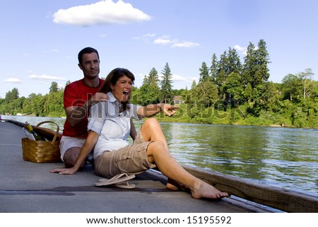 Happy couple laughing as they relax by the lake with a picnic basket next to them. Vertically framed photograph
