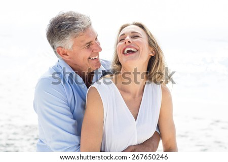 Happy couple laughing together at the beach #267650246