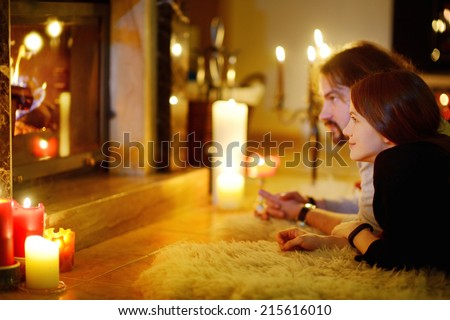 Happy couple laying by a fireplace in a cozy dark living room on Christmas eve