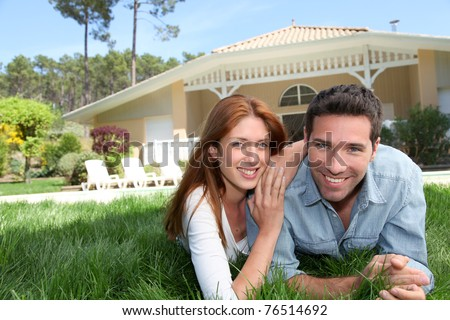 Happy couple laying down in their home garden