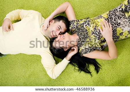 Happy couple laying on carpet at home